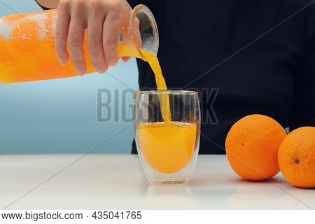 Female Hand Holding Glass Jar Of Fresh Squeezed Orange Juice And Pouring. Selective Focus