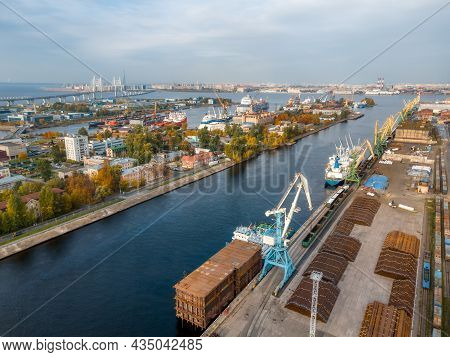 Aerial View On Seaport With Cranes And Ships On Dockside. Port Cranes Load Various Cargoes On Boats.