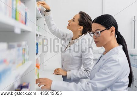 Cheerful Pharmacist In White Coat Reaching Carton Box With Medication Near Blurred Asian Colleague I