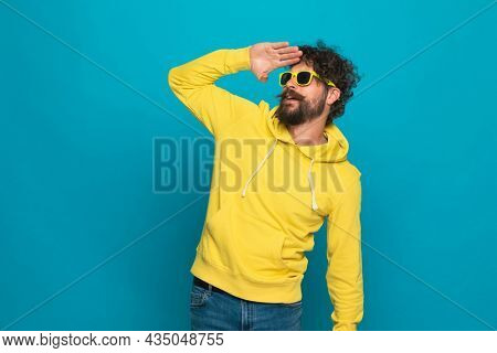 attractive unshaved guy in yellow sweatshirt with sunglasses holding hand to forehead and looking far away to side on blue background in studio