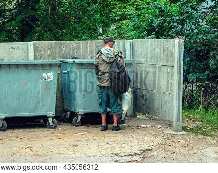 Poor And Hungry Homeless Man In Dirty Clothes Looking For Food In The Dumpster On The Urban Street I