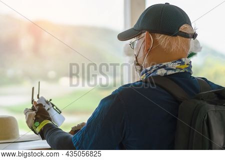 Back View Of Asian Old Male Engineer Doing Inspection Using Drone While Wear Face Mask To Avoid Coro