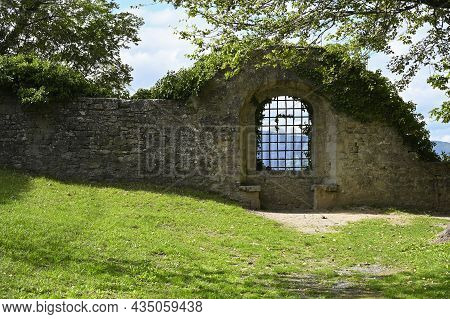 Magnificent Lattice Window In The Fortress Stone Wall Overlooking The Mountains, With A Green Lawn N