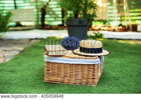 Wicker Picnic Basket  With Flowers On Grass In Garden. Weekend Concept. Picnic Basket With A Book An