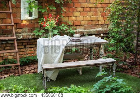 Garden In Summer With Patio, Wooden Garden Furniture And Barbecue. Dining Table In Backyard. Cozy Sp