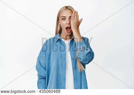 Portrait Of Blond Girl Cover One Side Of Face, Looking Impressed With One Eye, Gasping In Awe, Stand