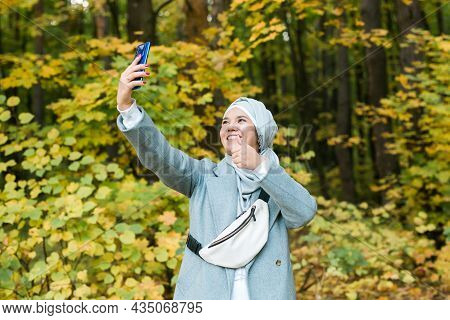 Young Arabian Muslim Woman In Hijab Clothes Doing Selfie Shot On Mobile Phone In Park. People Religi
