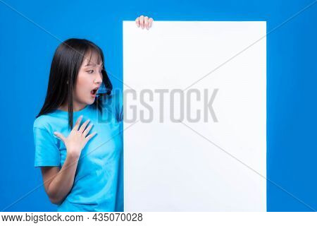 Excited Beautiful Asian Young Woman With Bangs Hair Style In Blue T Shirt Smiling And Looking A Blan