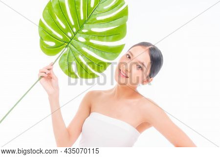 Beautiful Young Asian Woman  With Clean Skin ,fresh Skin Holding  Green Tropical Leaf In Hands On Wh