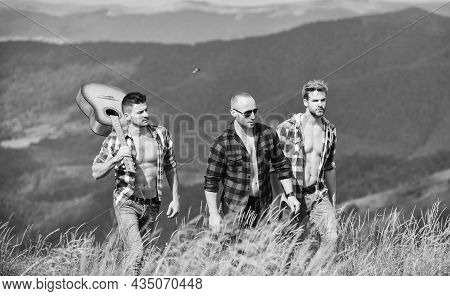 Enjoying Freedom Together. Group Of Young People In Checkered Shirts Walking Together On Top Of Moun