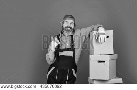 Man Wearing Boilersuit Packing Boxes. Move To New Apartment. Bearded Loader In Uniform. Cardboard Bo