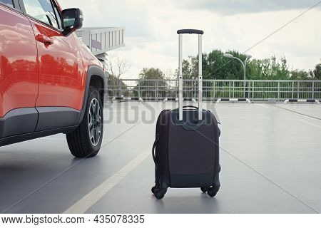 Suitcase And Car Parked Outdoors. Tourism Concept