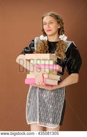 Upset Girl In School Uniform Holding Heavy Books. Overloaded Graduate Teenage Girl With Braided Hair