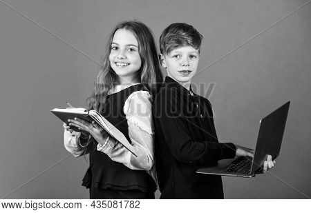 Primary School Pupils. Little Pupils Hold Book And Laptop Brown Background. Small Pupils Study At Sc