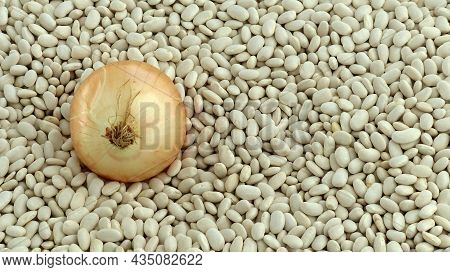 Close-up Large Onion Stands On White Dried Beans, Onions And Beans,