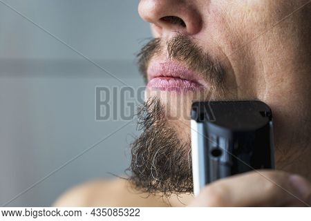 A Man Cuts His Beard And Mustache With An Electric Razor, Time To Shave, Beard And Mustache Care, Ba