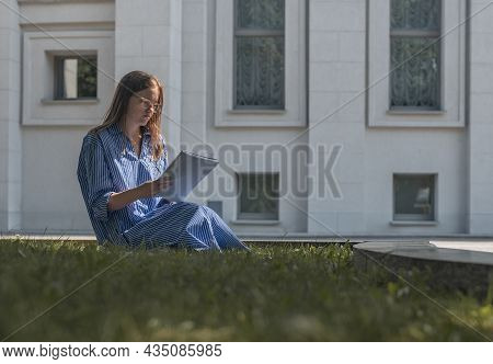 Young Student Sitting On Grass Near University Building, Learning And Reading, Holding Academic Lite