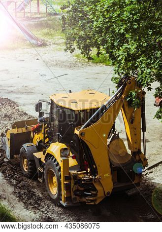 Yellow Excavator Loader Removes The Remains Of Broken Asphalt. High Quality Photo