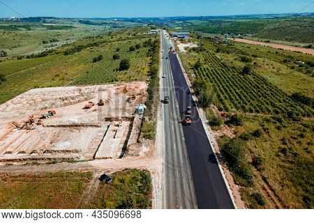 Aerial Top View Of Roadworks With Road Workers Lay Asphalt. Work On Laying Of Asphalt. Aerial Photog
