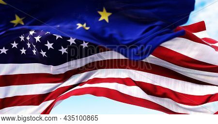 The National Flag Of The United States Of America Waving In The Wind With The European Union Flag Bl