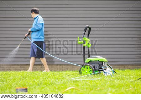 Washer Power Machine For Cleansing House On Yard With Blurred Background Of Man In Blue Cloth Clean