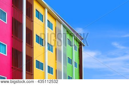 Low Angle And Side View Of Modern Colorful Building Against Cloud And Blue Sky Background