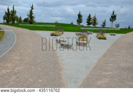 Square In The Park With Benches In The Shape Of Round Triangles Lined With Tiles In The Shape Of An