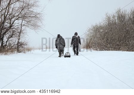 Two Fishermen Are Walking In Bad Weather Along A Snow-covered Path To A Frozen Pond. One Fisherman P