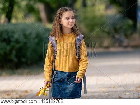 Preteen school girl with backpack holding yellow leaves in her hand and walking in autumn park. Pretty pupil female kid portrait outdoors