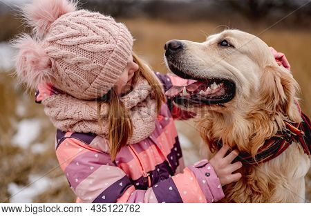 Little girl hugging golden retriever dog during walk on winter nature