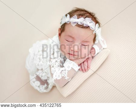 Closeup portrait of adorable newborn baby girl wearing beautiful white dress and wreath lying on her tummy and sleeping in studio. Cute infant child napping holding hands under cheeks