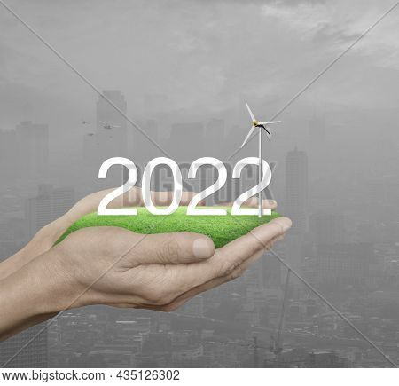 2022 White Text With Wind Turbine On Green Grass Field In Man Hands Over Pollution Modern City Tower