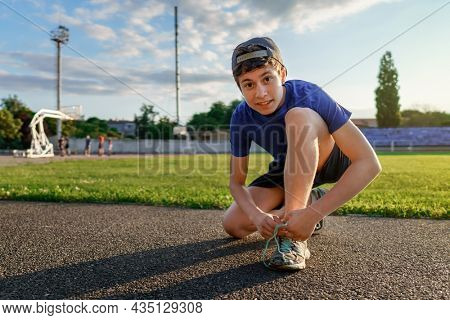 concept of sports and health - teen boy posing at a stadium track, he ties his shoelaces, a soccer field with green grass