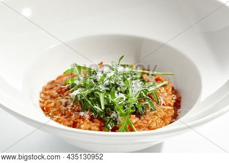 Vegan tomato risotto with ruccola on white plate. Italian dish - veggie risotto isolated on white background. Plant based dining. Clean eating in restaurant menu. Eat less meat. Vegetarian lunch