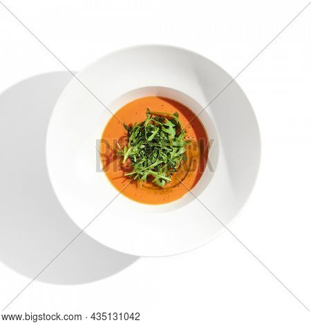 Summer Spanish soup - gazpacho with rocket salad isolated on white background. Vegetarian cold tomato soup in white plate. Meatless food in menu. Veggie lunch. Healthy food. Plant based eating