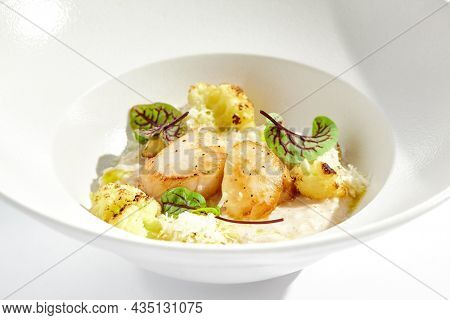 Delicious creamy risotto with sea scallop and cauliflower. Elegant main course with seafood on white plate. Grilled scallop with cauliflower and creamy rice. Seafood risotto with scallops