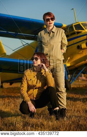 Two confident professional female commercial aviation pilots in uniform and sunglasses posing in front of their plane. Full length portrait on the airfield. Commercial aviation.