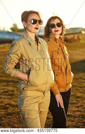Portrait of two gorgeous pilots women in stylish uniform and sunglasses posing on the airfield. Commercial aviation.