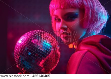 Disco style. Modern girl with bright glitter make-up and pink hair poses in the neon lights of the nightclub with a disco ball in her hands. Night party style.