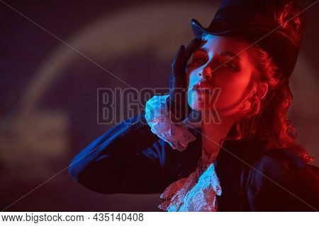 Refined young 19th century lady in an elegant authentic suit posing in a dark background with a huge moon behind her lit by mysterious red light. Style of the late 19th - early 20th century.