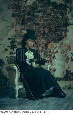 Vintage portrait of a beautiful exquisite young lady of the 19th century sitting in an armchair with a book. Historical reconstruction of the late 19th and early 20th century.