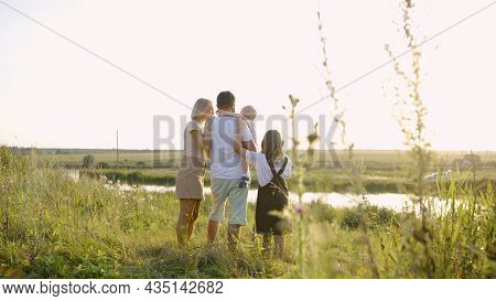 Happy Family Near The Lake At The Day Time. Concept Of Friendly Family. Husband And Wife Stand By Th