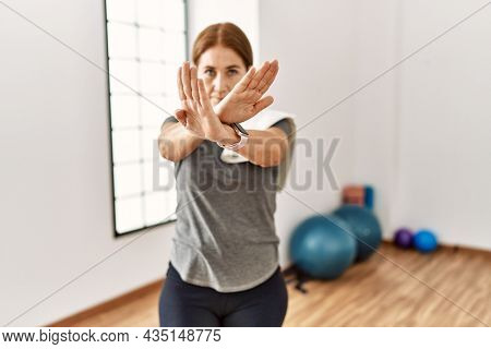Middle age woman wearing sporty look training at the gym room rejection expression crossing arms and palms doing negative sign, angry face
