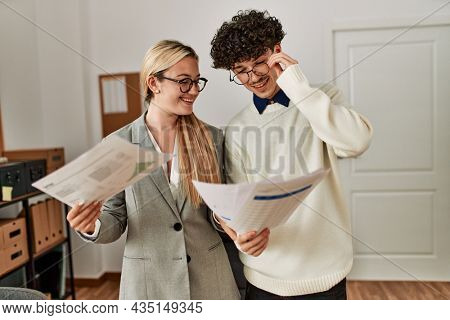 Two business executives smiling happy working at the office.