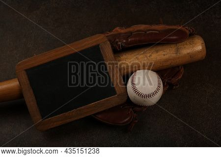 Close Up One Old Baseball Ball, Wooden Bate, Worn Leather Vintage Glove And Blackboard Sign On Grung