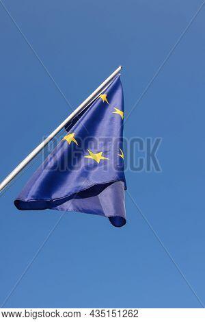 European Union Eu Flag Hanging On Flagstaff Over Clear Blue Sky, Symbol Of European Patriotism, Low