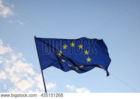 European Union Eu Flag Flying And Waving In The Wind Over Clear Blue Sky, Symbol Of European Patriot
