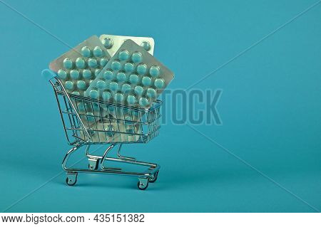 Close Up Several Different Blister Packs Of Pills In Small Shopping Cart Over Blue Background, Conce