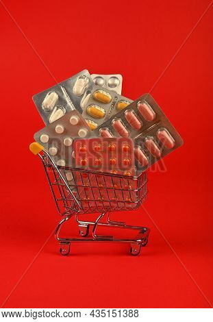 Close Up Several Different Blister Packs Of Pills In Small Shopping Cart Over Red Background, Concep