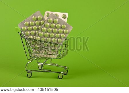 Close Up Several Different Blister Packs Of Pills In Small Shopping Cart Over Green Background, Conc